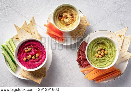 Colorful Hummus In Bowls, Served With Vegetables Sticks And Crackers. Traditional Hummus, Beetroot H