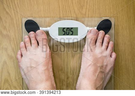 Man' S Feet On Weighing Scale. Diet Problems Concept With Weight Scale Spelling Sos. Person Standing