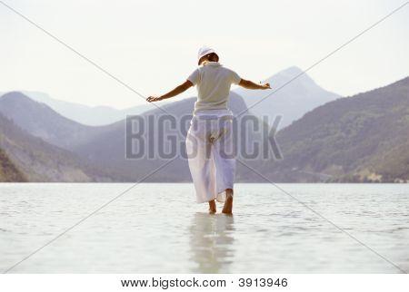Woman Tiptoeing Through Water By Mountains