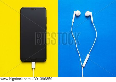 Smartphone With Blank Screen And Earphones On Blue And Yellow Background Top View. Headphones And De