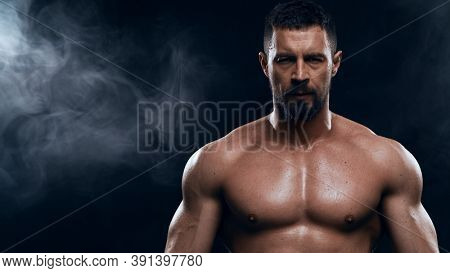 Fit and sporty bodybuilder over black background. Sportsman in studio. Sport and fitness concepts.