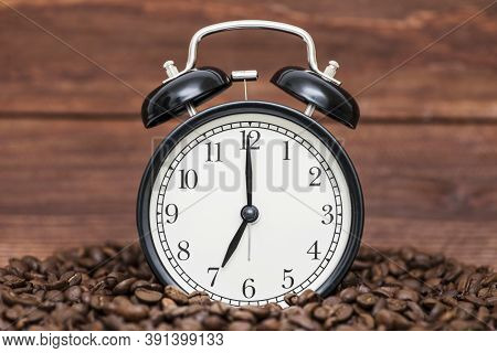Alarm Clock And Coffee Beans On A Wooden Background. Alarm Clock Standing On The Beans Of Coffee. Co