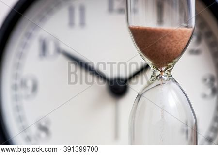 Hourglass On The Background Of Office Watch As Time Passing Concept For Business Deadline, Urgency A