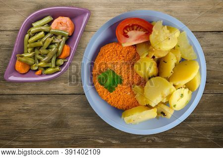 Meatball With Potatoes On Brown Wooden Background. Meatball With A Slice Of Tomato On Light Blue Pla