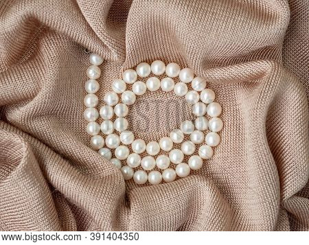 Glimmer Of Natural Pearl Beads Necklace On Abstract Beige Knitted Fabric Background. Pearl Necklace