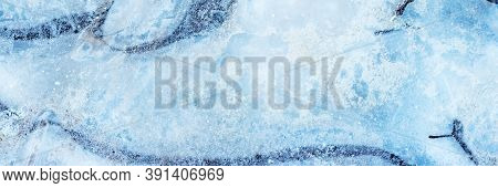 The Surface Of Natural Ice Covering The Puddle In Late Autumn. Ice Texture With Intersperses Of Whit