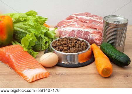 Dry Pet Dog Food With Natural Ingredients. Raw Meat, Fish, Vegetables, Eggs And Salad Near Bowl With