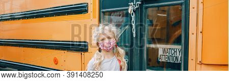 Sad Girl Student With Face Mask Near Locked Yellow Bus. Closed School During Pandemic And Quarantine