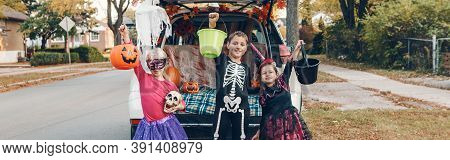 Trick Or Trunk. Brother And Sisters Celebrating Halloween In Trunk Of Car. Children Kids Friends Pre