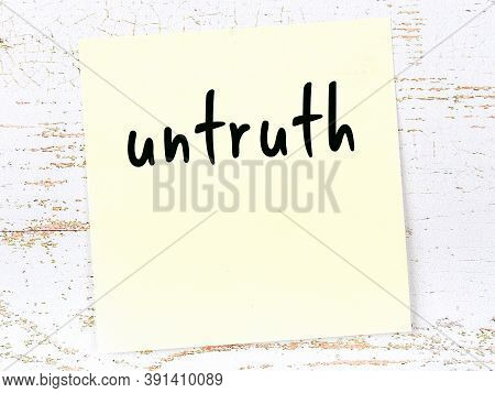 Yellow Sticky Note On Wooden Wall With Handwritten Inscription Untruth