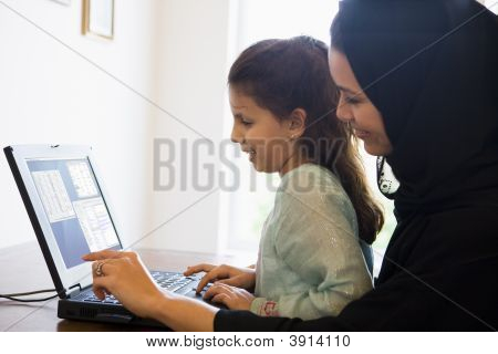 Middle Eastern Woman And Child Sat In Home Office Using Laptop