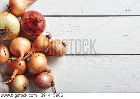 Yellow And Red Onions On A White Wooden Background. Top View.