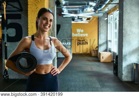 Portrait Of A Young Beautiful Fitness Woman In Sportswear Holding Yoga Mat And Smiling At Camera Whi