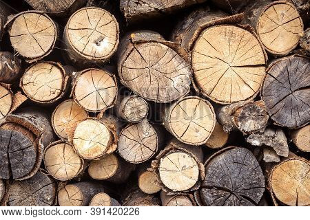 Firewood Pile, Pattern With Ends Of Logs Close-up. Woodpile Of Brown Timber, Stack Of Rough Sawn Tre