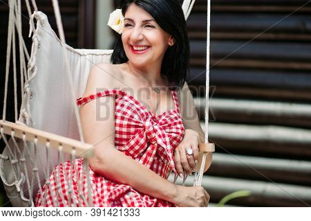 Brunette Middle Aged Woman In Red Checkered Dress And White Flower In Her Hair
