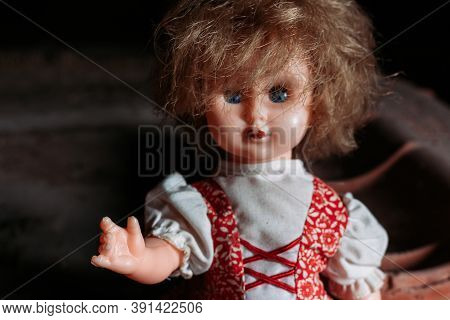 Old Doll Sitting On Dirty Ground. Scary Look. Halloween Concept
