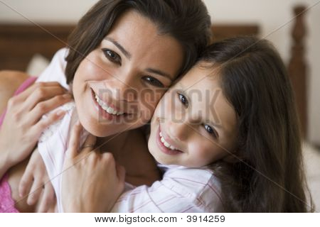 Middle Eastern Woman On Bed With Daughter At Home