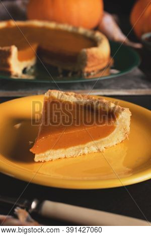 Orange Pumpkin Pie For Thanksgiving. A Slice Of Pumpkin Pie On A Yellow Plate Close-up On A Dark Bac