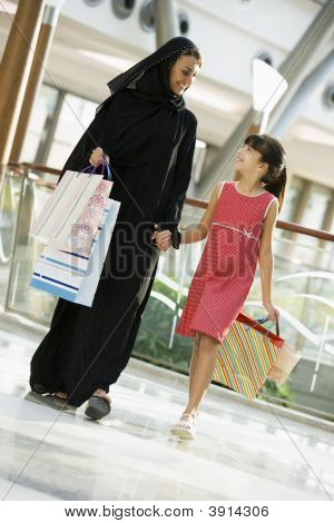 Middle Eastern Woman And Child Walking Through Shopping Mall With Bags