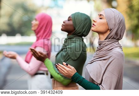 Three Muslim Women Praying Together Standing Outdoors Wearing Traditional Hijab Headscarf And Modern