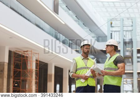 Portrait Of Two Mature Building Contractors Discussing Work While Standing On Construction Site, Cop