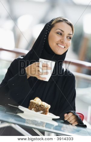 Middle Eastern Woman Eating And Drinking In Shopping Mall