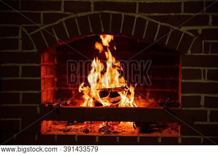 Fire In A Fireplace. Wood Burns In A Cozy Fireplace At Home