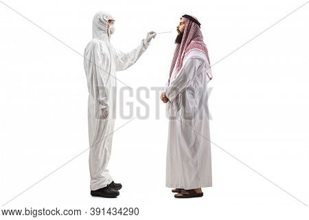 Full length profile shot of an epidemiologist in a hazmat suit  taking a cotton swab test from an arab man isolated on white background