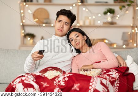 Boring Christmas. Bored Asian Family Couple Watching Movie On Tv Holding Television Remote Control,