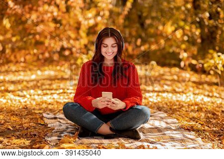 Pretty Young Woman Sitting On Picnic Blanket At Autumn Park With Headphones And Mobile Device And Li
