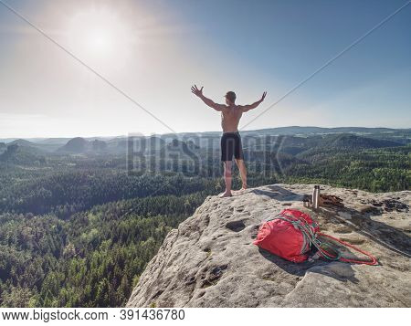 Shirtless Sportsman Take Off Backpack And Rope On Top Of The Mountain And Raised Arms To Greeting Na