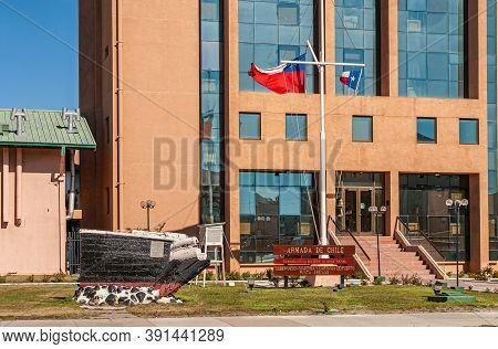 Punta Arenas, Chile - December 12, 2008: Flags, Sign, And Ship Bow Statue In Front Of Light Brown St