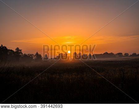 Orange Sunrise Over A Meadow In Fog.