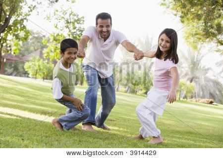 Middle Eastern Man Being Pulled Around By Children In Park