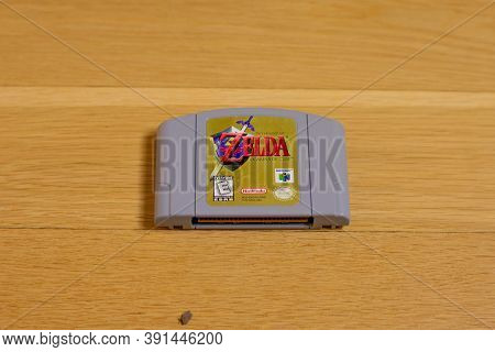 A Nintendo 64 Cartridge Of The Legend Of Zelda Ocarina Of Time, A Popular Retro Title, On A Wood Flo