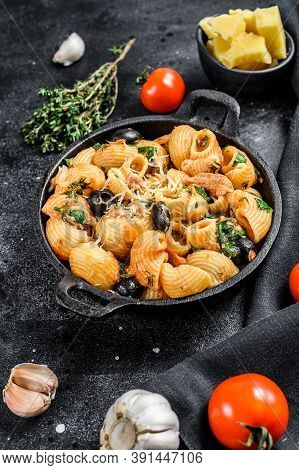 Conchiglie Rigate Pasta Puttanesca With Anchovies, Tomatoes, Garlic And Black Olives. Black Backgrou