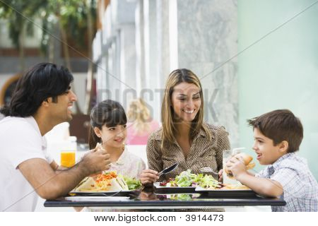 Middle Eastern Family Eating And Drinking In Shopping Mall