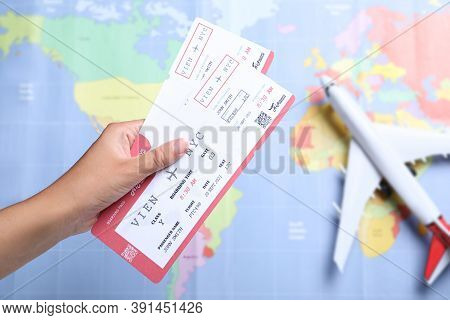 Woman Holding Airline Tickets Above World's Map With Toy Plane, Closeup. Travel Agency Concept