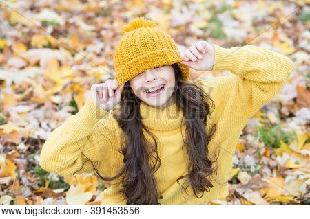Happy Teenage Kid Having Fun In Autumn Forest With Beautiful Seasonal Maple Leaves Wearing Warm Knit