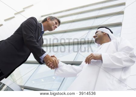 Middle Eastern And Western Business Men Shaking Hands