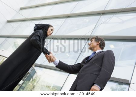 Middle Eastern Business Woman And Western Man Shaking Hands Outside Offices