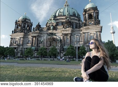 Thoughtful Girl Tourist Sitting In Germany Near Berlin Cathedral. Berlin Cathedral View In Germany W