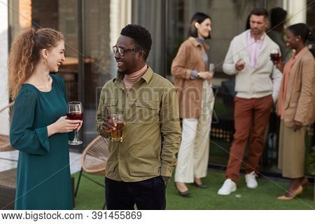 Multi-ethnic Group Of Contemporary Adult People Chatting While Enjoying Outdoor Party At Terrace, Co
