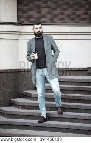 Hipster Hold Paper Coffee Cup And Enjoy Urban Environment. Drink It On The Go. Man Bearded Hipster P