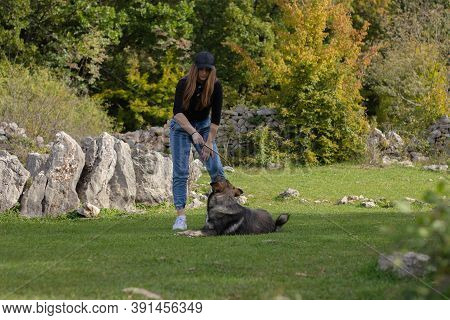 Brunette Girl Playing With A Wild Dog In A Field Surrounded By Rocks. Holding A Stick That The Dog I