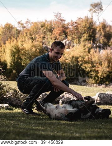 Split Croatia October 2020 Vertical Shot Of A Man Petting A Brown Dog On Its Stomach, Dog Enjoying I