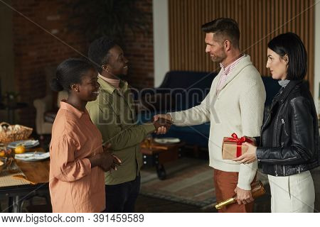 Side View Portrait Of Elegant African-american Couple Welcoming Guests For Dinner Party At Home, Cop