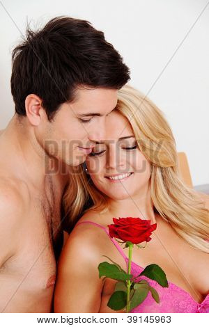 a romantic couple in bed with rose. marry the man.