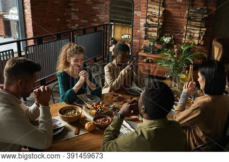 High Angle Portrait Of Multi-ethnic Group Of Elegant Young People Praying With Eyes Closed While Sit