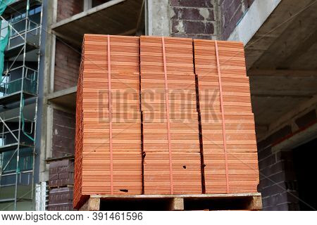 A Stack Of Red Hollow Bricks At A Construction Site. Material For Construction And Repair. Clay Bric